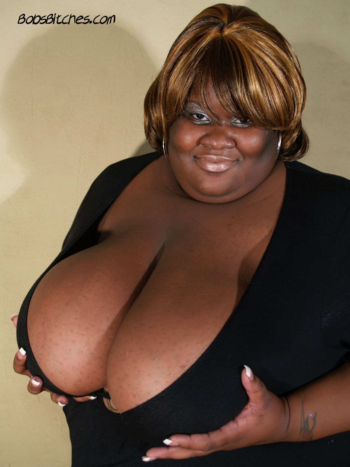 Monstrous ebony bbw with monster tits exposes her deep cleavage.