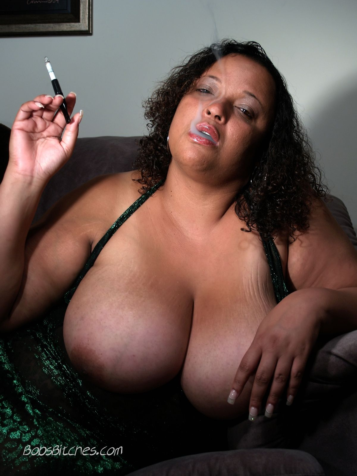 Big tit ebony bbw is smoking a cigarette with tits hanging out of her tight dress