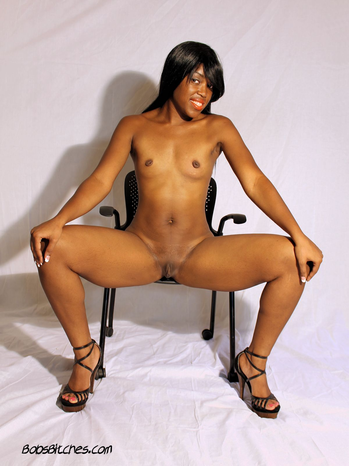Dominican ebony milf, Arva Nalga, is naked wearing only high heels.