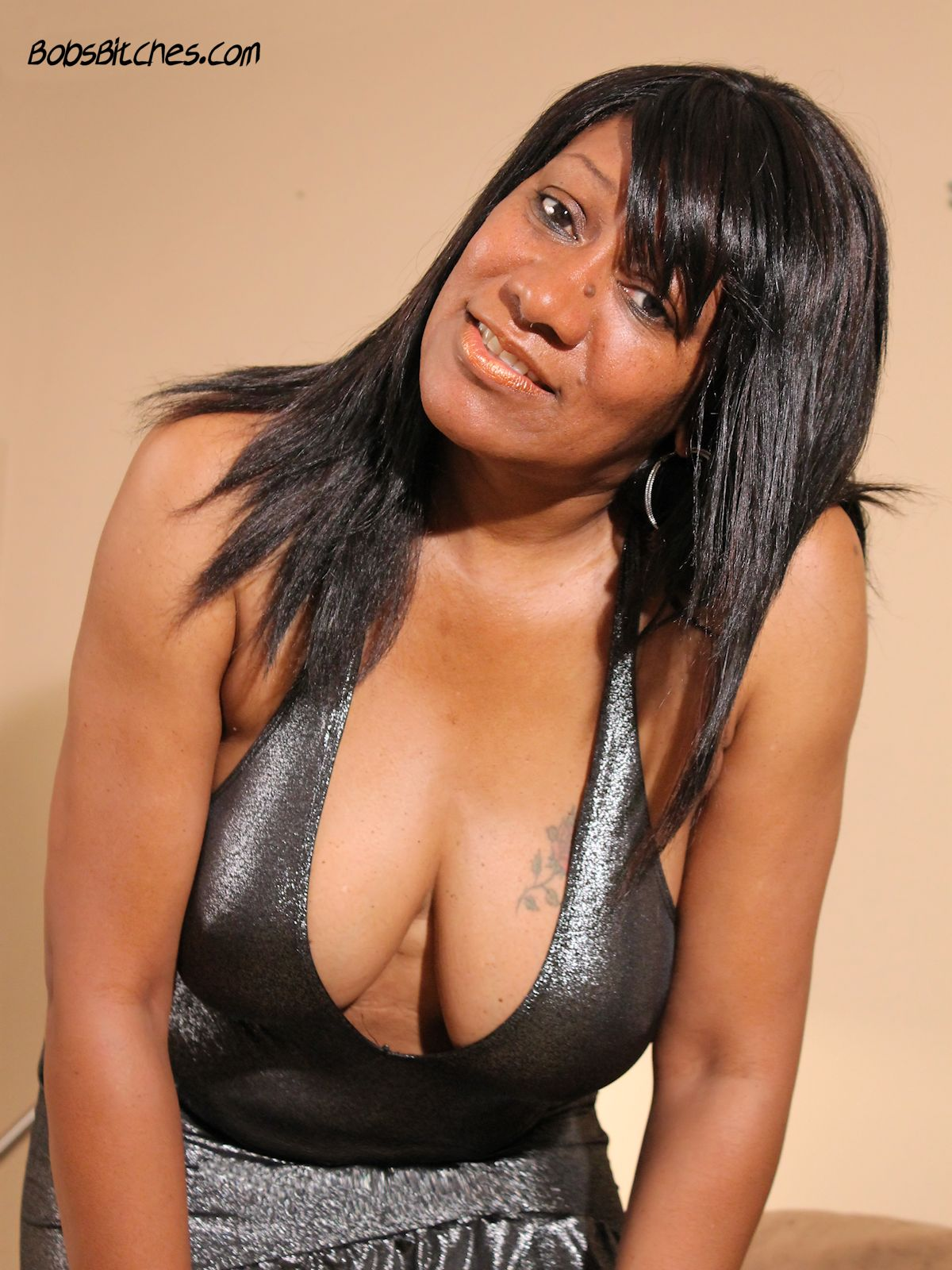 Ebony mother and milf reveals her big tits and cleavage.