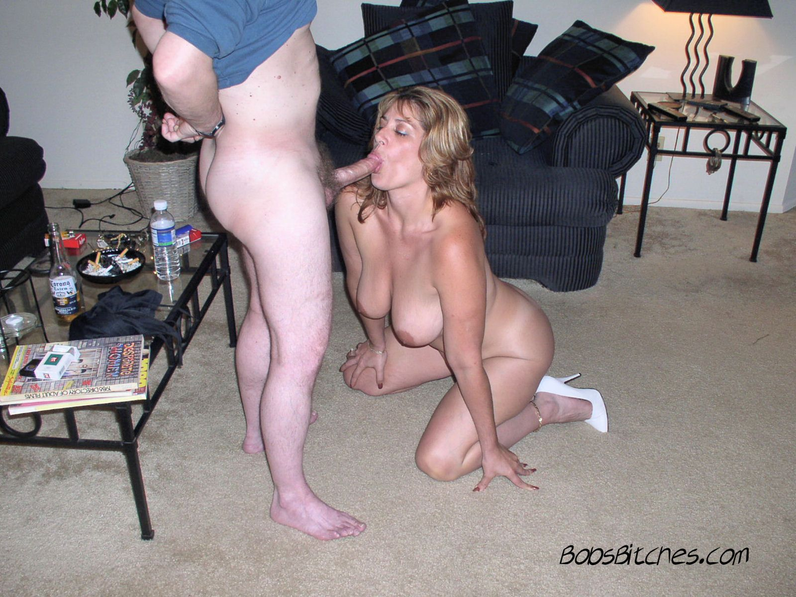Big tits swinger, and wife, Ashley, gets on her knees naked to blow Bob. Wearing high heels only.