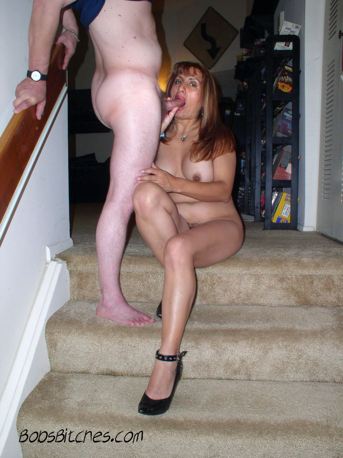 Latina milf sucks cock sitting on the stairs wearing only high heels.