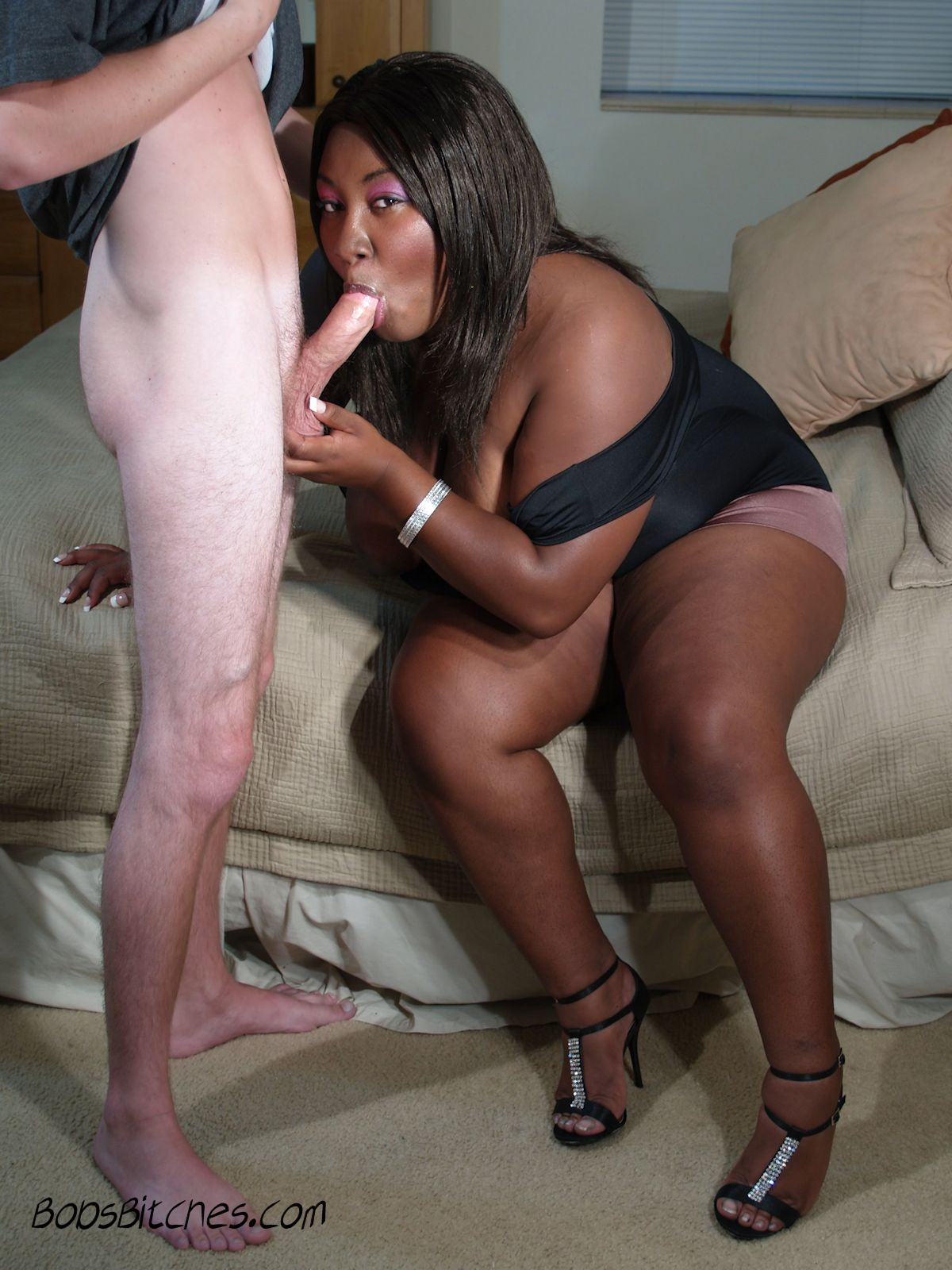 High heeled ebony babe sucks a big white cock .
