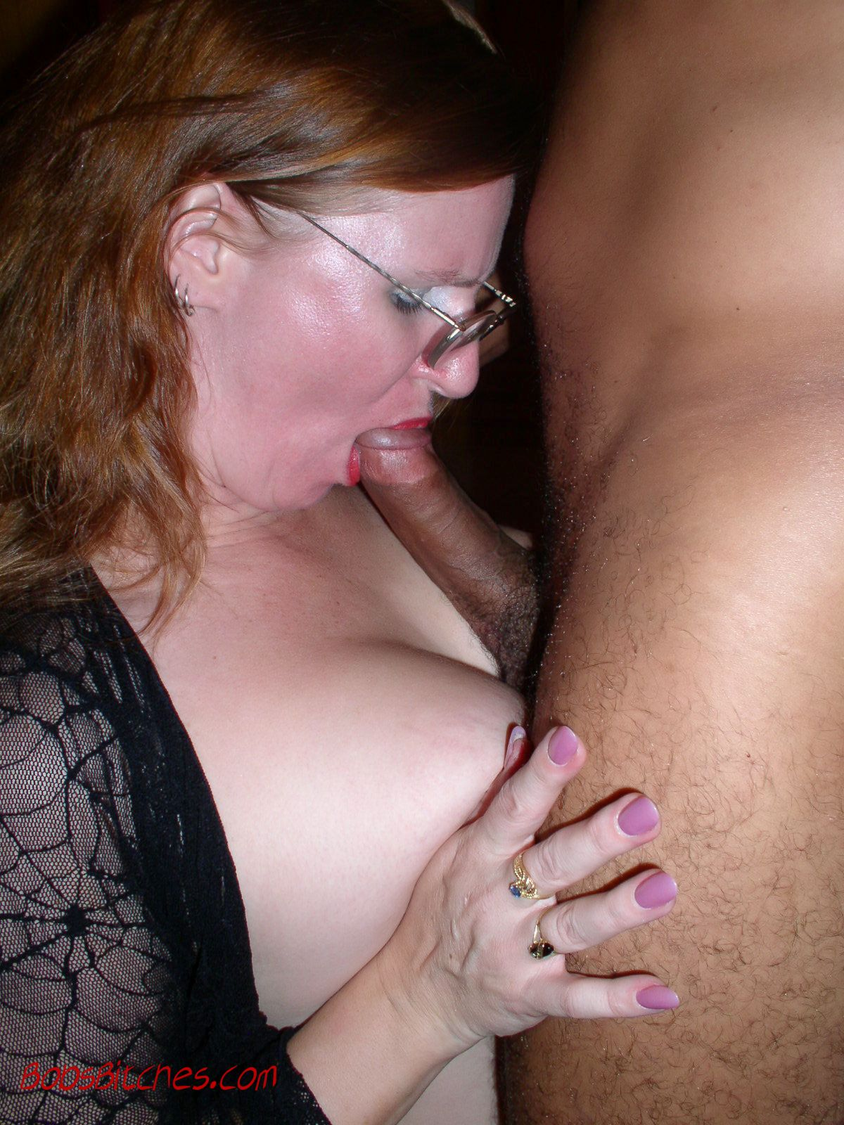 Redhead swinger wife wearing glasses is doing a blow job on a big black cock.