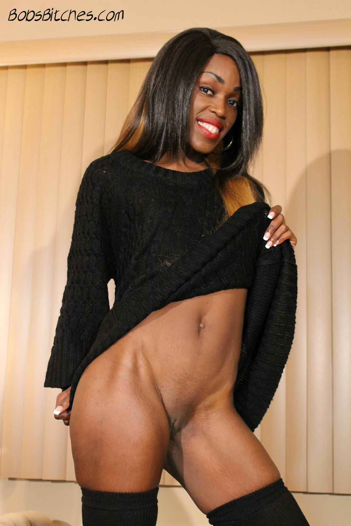 Dominican ebony beauty, Arva Nalga, pulls up her skirt to show her bald pussy.